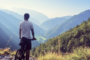 山を見下ろす男性と自転車